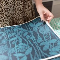 Hands holding hand printed wallpaper