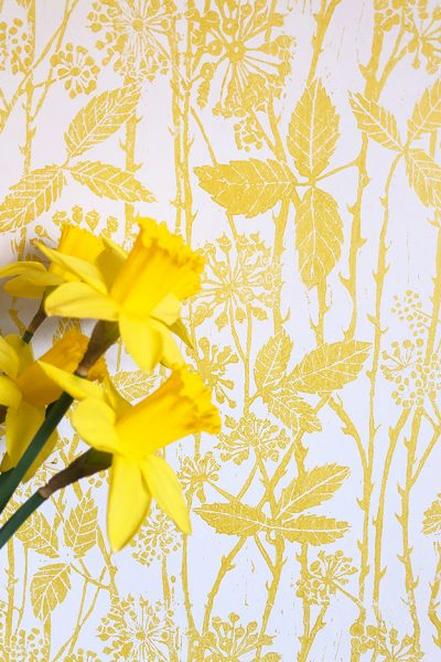 Hand printed wallpaper in yellow and white.