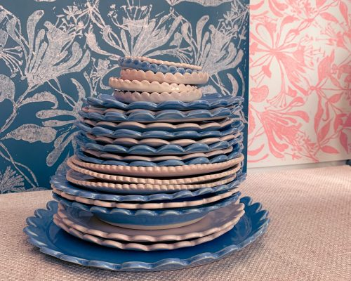 Ceramic plates in front of hand printed wallpaper